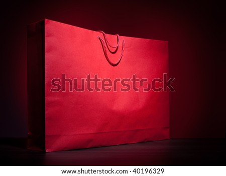 Big red shopping paper bag on dark red background - stock photo