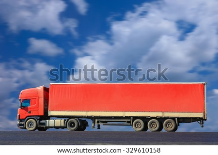 big red truck goes on the way to sky background - stock photo