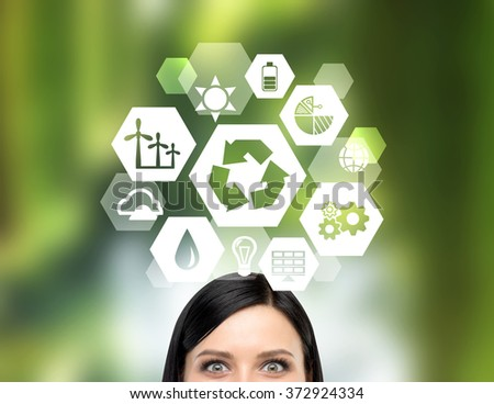 big 'reduce, reuse, recycle' sign over a woman's head. Front view, only eyes seen. Blurred green background. Concept of clean energy. - stock photo
