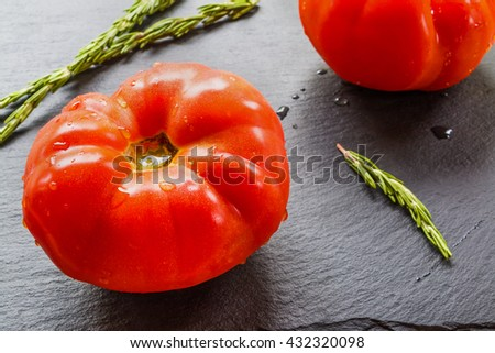 Big ripe tomatoes and rosemary on dark stone background. Selective focus. - stock photo