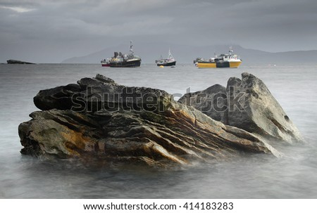 Big rock near Elgol with fishing boats on background in stormy weather, Isle of Skye, Scotland