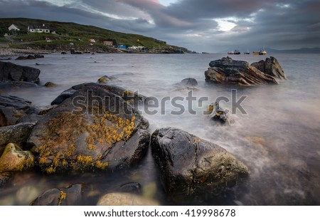 Big rocks in Elgol harbor with boats in background, Isle of Skye, Scotland - stock photo