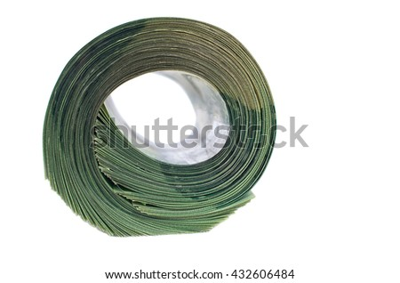 Big roll of green banknotes isolated on wooden background