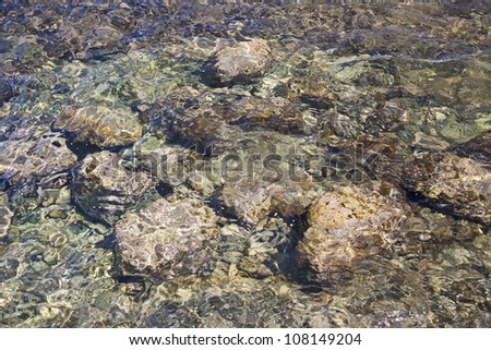Big round stones under clear sea water. - stock photo