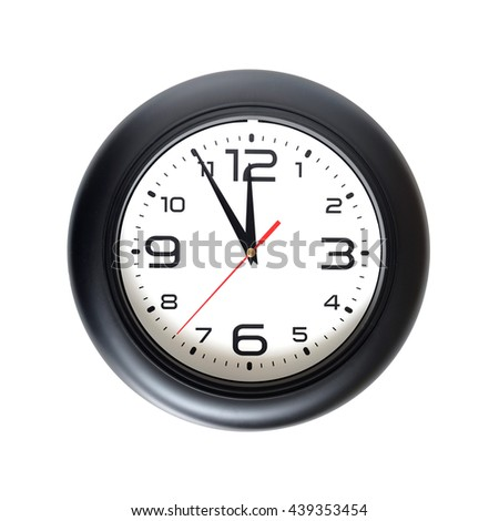 Big round wall clock, with a black rim isolated on white background close-up and arrows showing almost twelve o'clock - stock photo