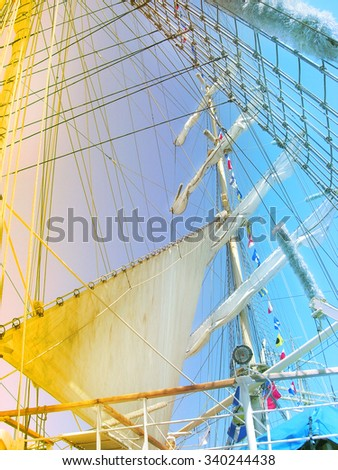 Big sails of sail ship.  Details of the mast and sail from an old sailing ship with red -  blue gradient effect. - stock photo
