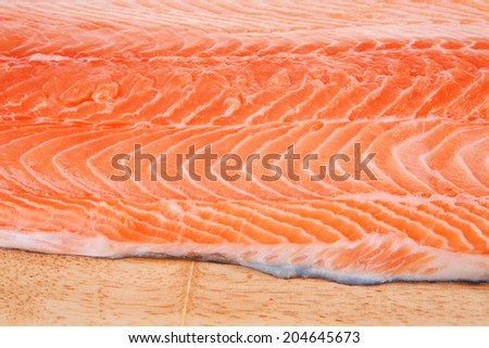 big salmon chunk on wooden plate over white