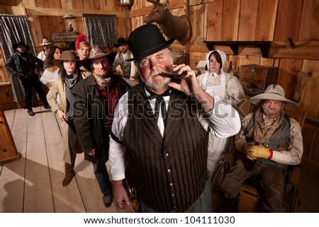 Big saloon owner with cigar and customers behind him - stock photo