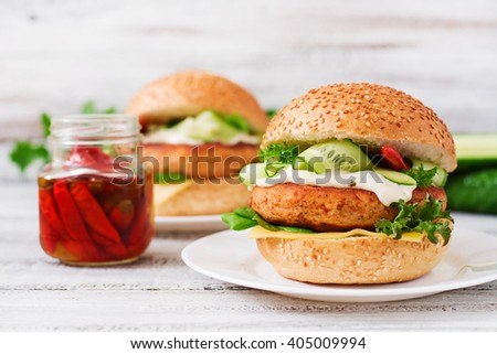 Big sandwich - hamburger with juicy chicken burger, cheese, cucumber, chili and tartar sauce on a light wooden background - stock photo