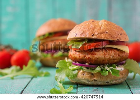 Big sandwich - hamburger with juicy chicken burger, cheese, tomato,  and red onion on wooden background