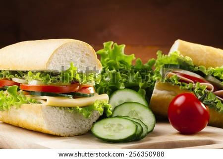 big sandwich with ham, cheese and vegetables on woodboard - stock photo