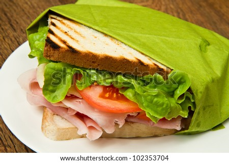 big sandwich with ham, cheese, tomatoes and salad on toasted bread - stock photo