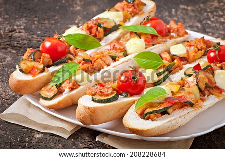 Big sandwich with roasted vegetables (zucchini, paprika , tomatoes) with cheese and basil on old wooden background - stock photo