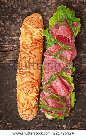 Big sandwich with salami, lettuce and arugula - stock photo
