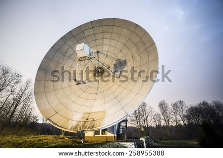 Big satellite dish with which signals are transmitted to or received from a communications satellite. - stock photo