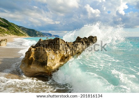 Big sea wave breaking on the beach rocks with a high sea spray - stock photo