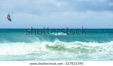 Big sea waves and kite-surfer enjoying extreme water sport  - stock photo