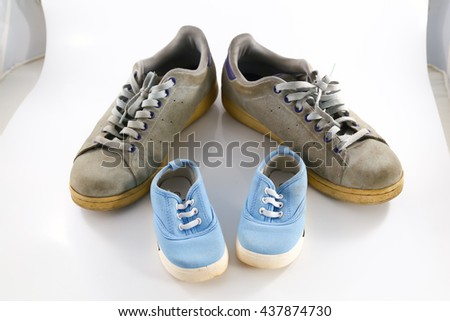 big shoes of father and small baby shoes - stock photo