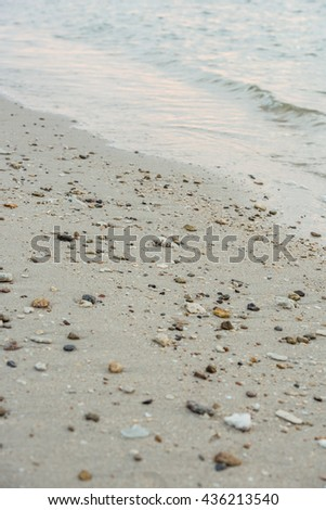 Big shot the sandy stretch of beach covered with pebbles and stones on which the lapping waves of the sea