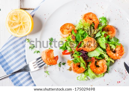Big shrimps with lettuce leaves and thyme dressing with lemon juice - stock photo