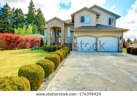 Big siding house with garage and high column porch. Green lawn with trimmed hedges and red bushes make the curb appeal stand out - stock photo