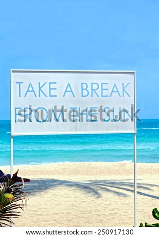 """Big sign standing on the beach with the words ; """"Take a break from the sun."""" . This too remind people to go out of the sun in the middle and hottest of the day.    - stock photo"""