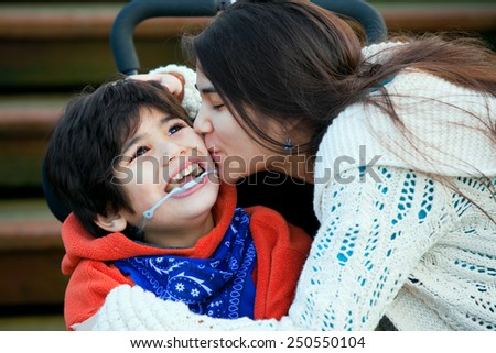 Big sister kissing disabled little brother seated in wheelchair on cheek - stock photo