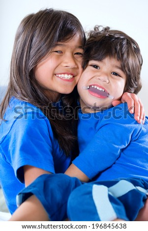 Big sister taking care of her disabled little brother - stock photo