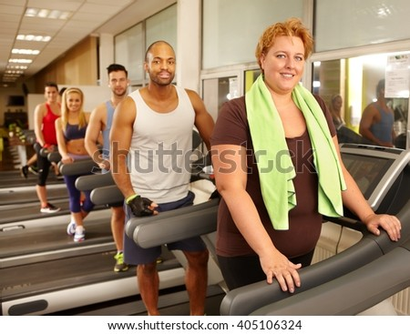 Big size woman training on running machine in gym with others.