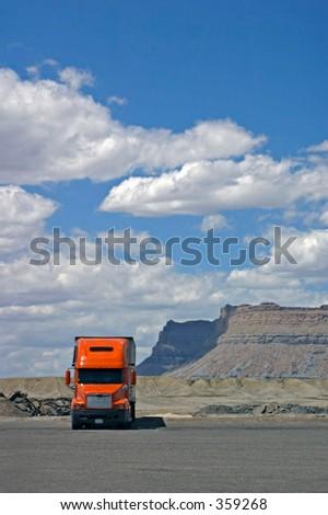 Big Sky over Orange Tractor Trailer - stock photo