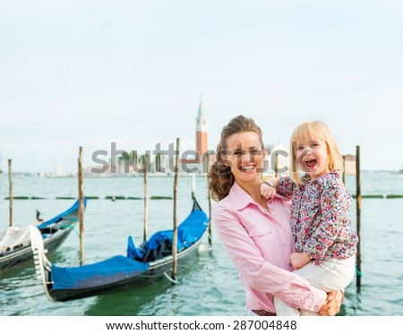 Big smiles for daddy... This little girl is thrilled to be in Venice with her parents. Gondola rides are so much fun. - stock photo