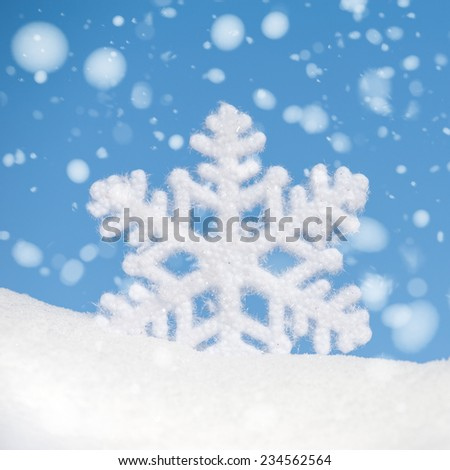 big snowflake toy with snowfall on blue sky background - stock photo