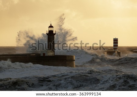 Big splash from stormy sea waves against pier and lighthouses at winter sunset. Entry of Douro river mouth harbor, north of Portugal. Soft backlighting.