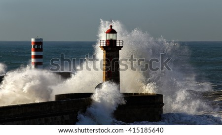 Big splashing waves with spray over piers and beacons of Douro river mouth in a sunny morning, Porto, north of Portugal
