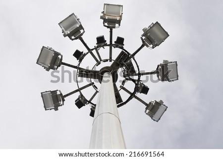 Big spotlight pole on blue sky background. - stock photo
