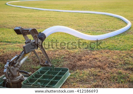 Big sprinkler and water hose in grass field football stadium