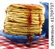 Big stack fresh pancakes with syrup on checkered napkin - stock photo