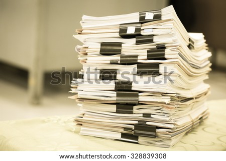 Big stack of business report paper files with black clips