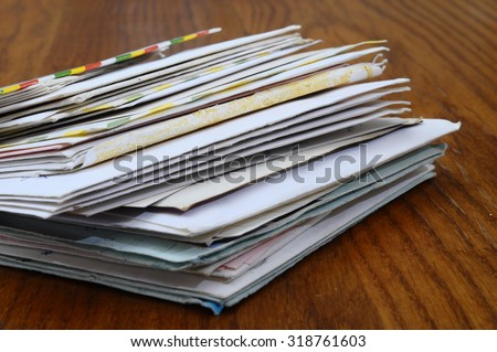 Big stack of mails, pile of papers, or heap of letters waiting on wooden table