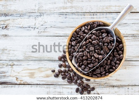Big stainless steel scoop of coffee beans on white wooden table - stock photo