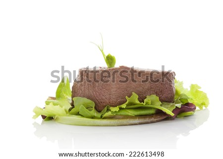 Big steak on green salad isolated on white background. Culinary beefsteak eating. Filet mignon, tenderloin steak. Red meat. - stock photo
