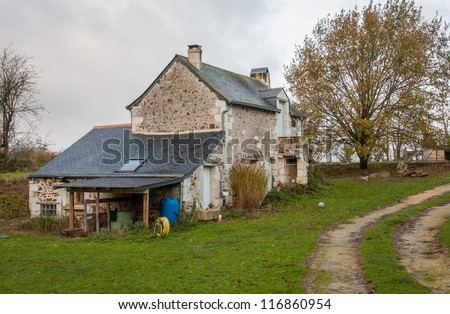 Big stone farmhouse on green grass with big tree on its side and next to it a pathway on a gray weather - stock photo