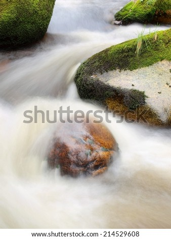 Big stones in foamy water of rapid stream. Light blurred water bended between boulders.