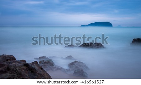 Big stones on the beach, with calm water and early morning cloudy sky background