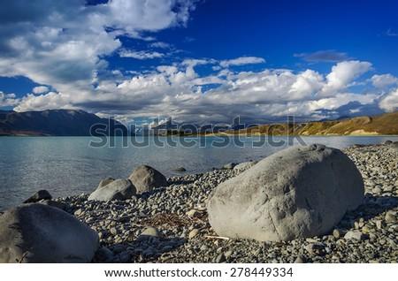 Big stones on the shore Lake Tekapo on a background of mountains. South Island, New Zealand - stock photo