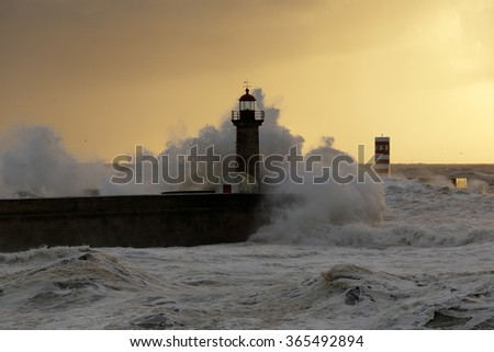 Big stormy sea waves over pier and lighthouses at winter sunset. Entry of Douro river mouth harbor, north of Portugal. Soft backlighting. - stock photo