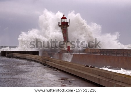 Big Stormy Wave against pier and old lighthouse. Foz do Douro Harbor. - stock photo