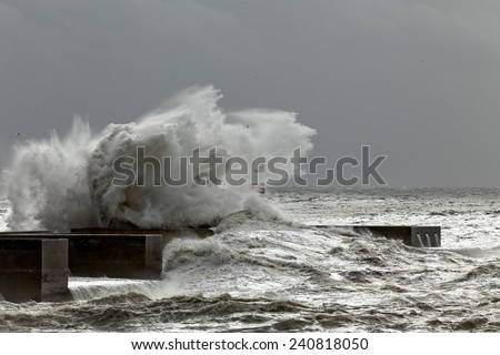 Big stormy wave over pier and beacon, north of Portugal - stock photo