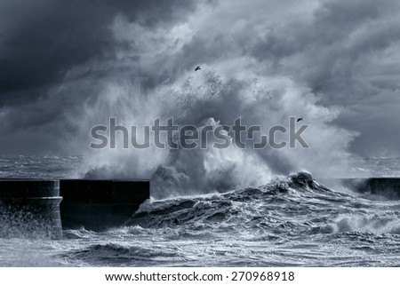 Big stormy waves against pier from the north of Portugal. Enhanced sky. Black and white toned blue.  - stock photo
