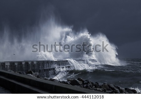 Big stormy waves over a pier and lighthouse, Porto, Portugal. Toned blue.